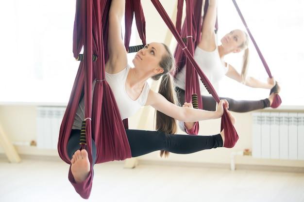 Parivrtta upavistha konasana yoga pose in hammock