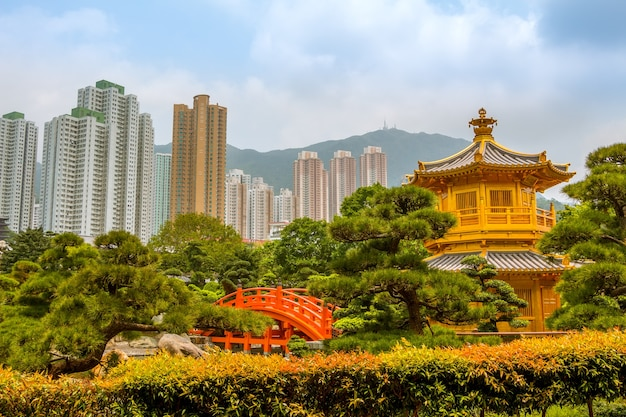 Park in hong kong. golden pavilion surrounded by plants and trees. skyscrapers and mountains in the background
