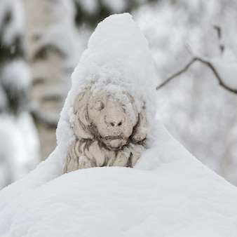 Park sculpture of a lion covered with snow in blizzard