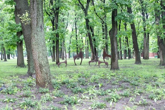 사슴 가족과 함께 나무와 동상이 있는 공원