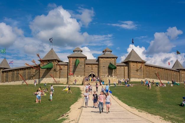 Парк с гуляющими людьми на фоне искусственной крепости из бревен