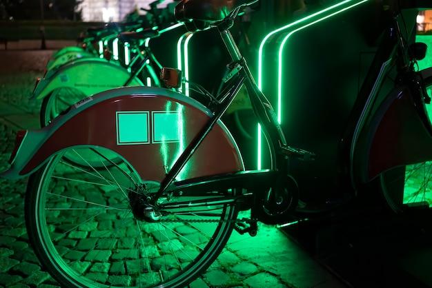 Biciclette parcheggiate per la condivisione con la notte di illuminazione verde a bucarest, romania