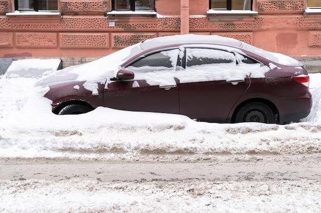 눈이 내린 후 청소되지 않은 눈 덮인 도로에 눈이 덮여 주차 된 차량. 나쁜 겨울 날씨, 강수량 증가 및 눈 수준 개념.