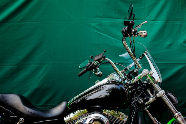 Parked motorbike in front of green background