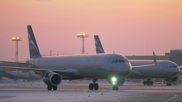 Parked and taxiing planes at sheremetyevo airport in moscow evening winter view