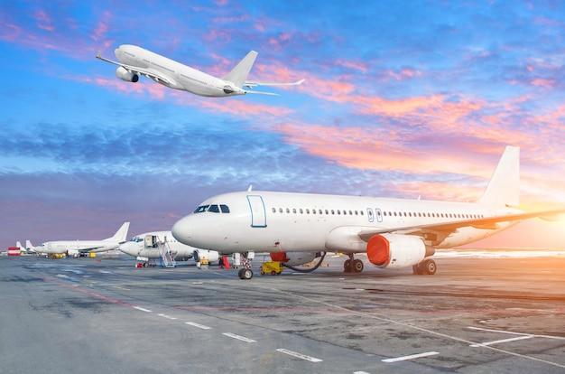 Парковка в аэропорту с взлетающими самолетами и солнцем в вечернем небе.