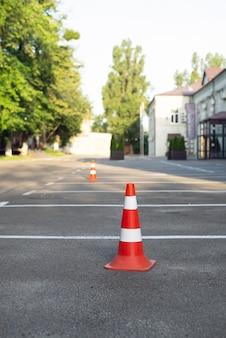 アスファルトのパーキングコーン通りに立っているプラスチック製のオレンジ色のパーキングコーン