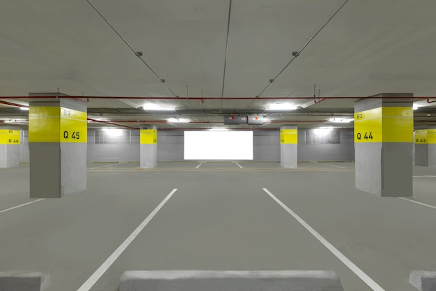 Parking garage underground interior with blank billboard.
