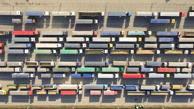 港湾ターミナルで荷降ろしするためのトラックの列に駐車する。農産物の物流輸送。