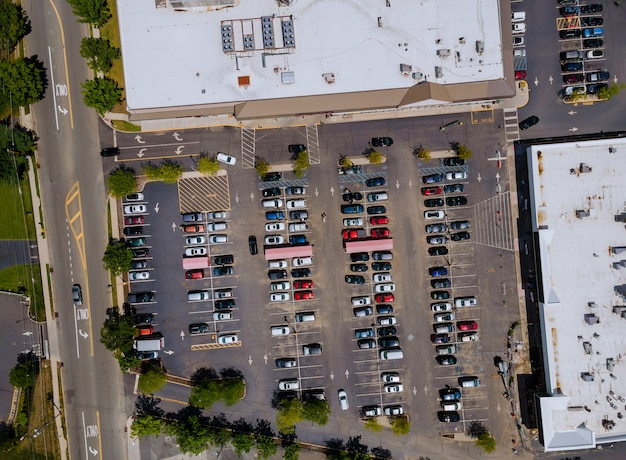 The parking lot is almost completely filled with colorful cars near on shopping center from the height of bird flight.