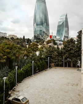 Parcheggio vicino agli alberi con vista sulla città di grattacieli