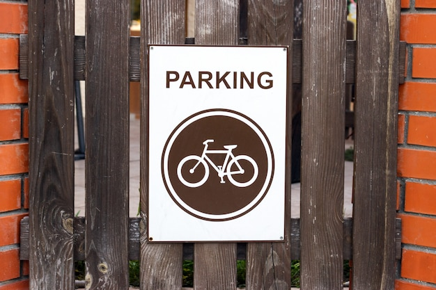A parking place for bicycles, a sign on a wooden fence