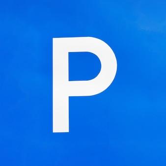 青い空を背景に駐車場サイン。道路標識と規制。