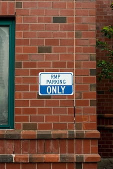 Parking sign on brick wall front view