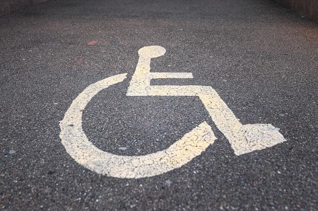 Парковочный знак для инвалидов на асфальте. горизонтальное фото