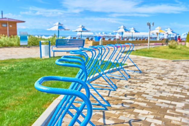 Parking spaces for bicycles on the ocean front on the background of beach umbrellas