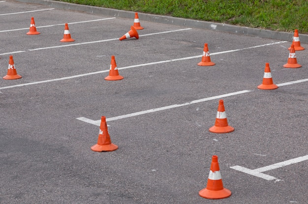 Parking spots with road marking and orange safety cones standing