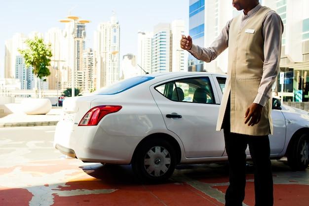 Il valet di parcheggio in vestito del beoge si leva in piedi davanti a peugeout bianco