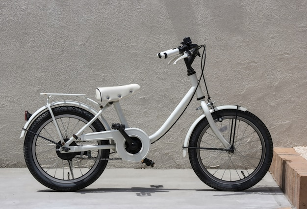 A parking white child bicycle with cement wall as background.