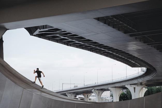 パルクール選手が橋を登る。街中でのフリーランニング