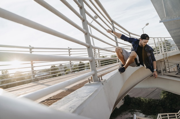 Parkour athlete hanging on the bridge and ready for dangerous jump. freerunning in the city