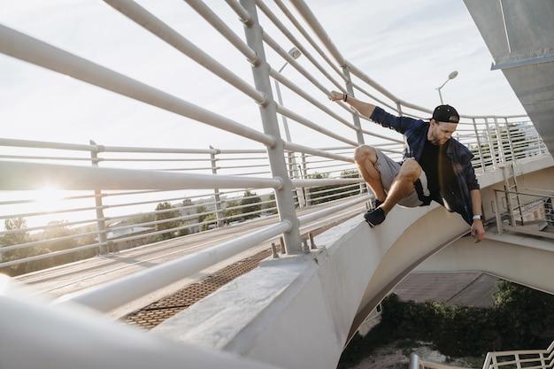 橋にぶら下がって危険なジャンプの準備ができているパルクールアスリート。市内でのフリーランニング