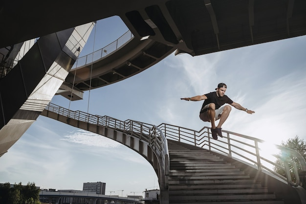 Parkour athlete training in the city. man performs a big freerunning jump through the stairs.
