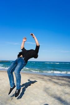 ビーチでフリップまたは宙返りをしているパルクールの男フリップを始めた瞬間の凍結