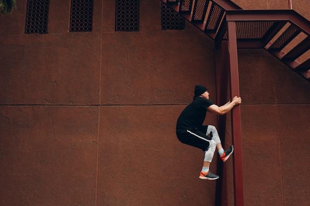 パルクールの若い男がアクロバティックなトリックを作ってジャンプジャンプ高