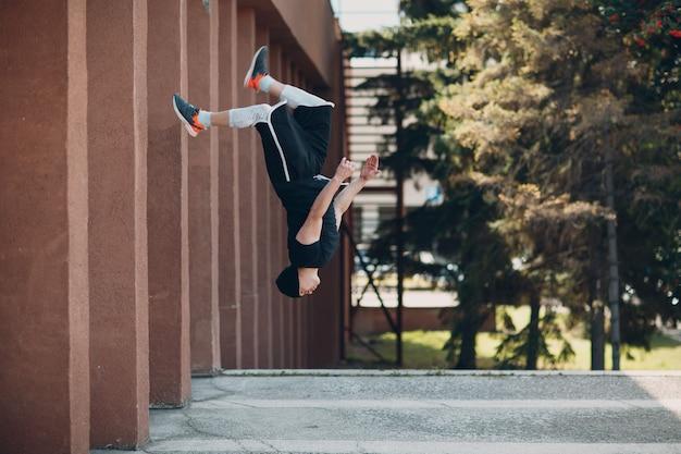 アクロバティックなトリックとフリップジャンプを高くするパルクールの若い男