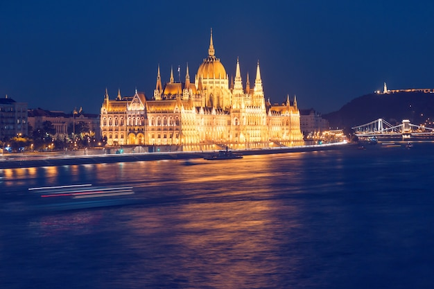 Parliament building of budapest above danube river in hungary at night, neo-gothic style architecture
