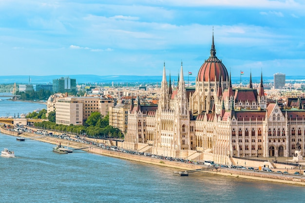 Parliament and riverside in budapest hungary with sightseeing ships during summer day with blue sky and clouds