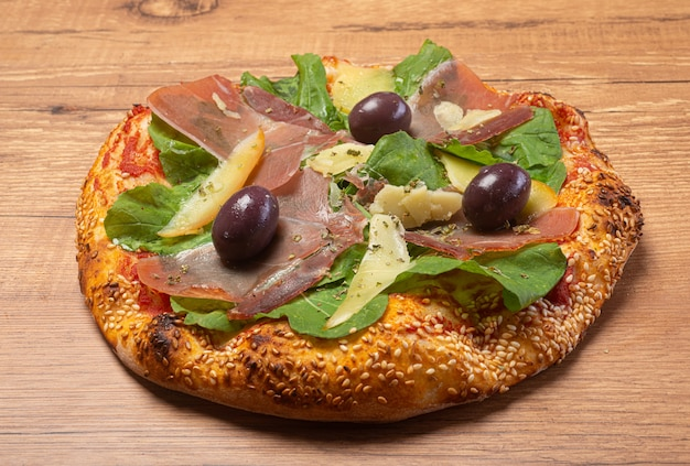 Parma ham, parmesan and arugula pizza served on a rustic wooden table.