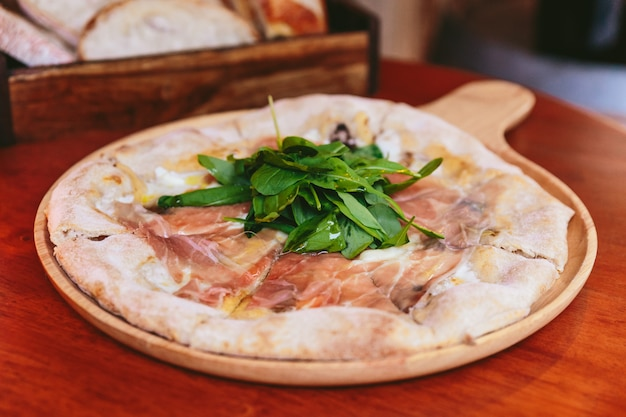 Parma ham pizza topping with rocket on rounded wooden plate with sliced bread in wooden box in the background.