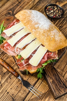 Сэндвич с пармской ветчиной на хлебе чиабатта с рукколой и сыром бри камамбер. деревянный стол. вид сверху.