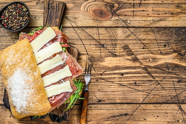 Сэндвич с пармской ветчиной на хлебе чиабатта с рукколой и сыром бри камамбер.
