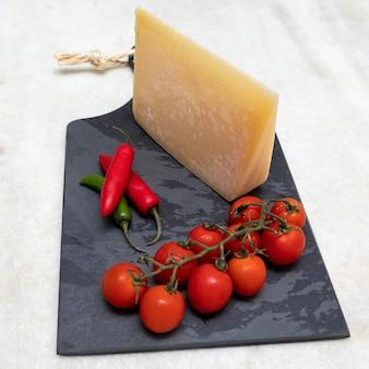 Сыр пармезан на черной каменной доске со специями