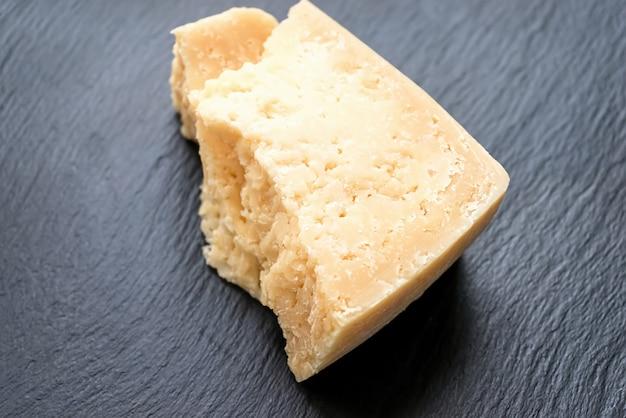 Сыр пармезан на черном камне. вид сверху