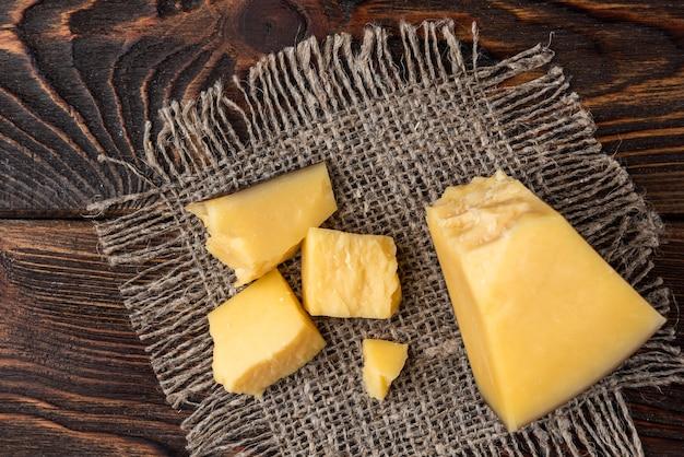 Сыр пармезан на темном деревянном фоне.