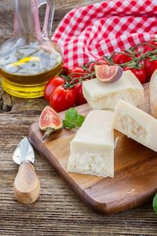 Сыр пармезан на деревянной разделочной доске с помидорами черри