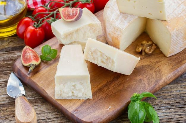 Сыр пармезан на деревянной разделочной доске с инжиром и помидорами черри