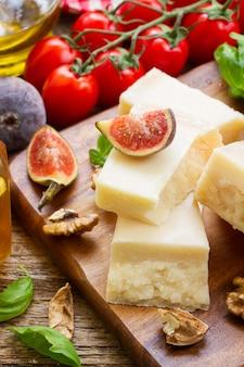 Сыр пармезан на деревянной разделочной доске с грецкими орехами и помидорами черри