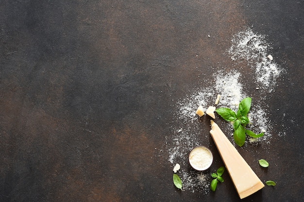Parmesan cheese with basil on a concrete background. ingredients for the sauce, top view.