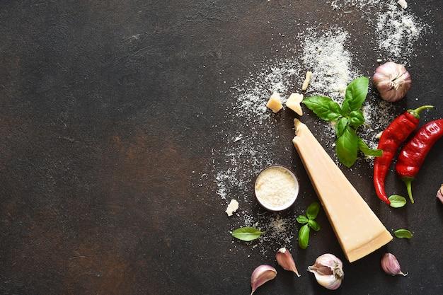 コンクリートの背景にバジル、ニンニク、唐辛子とパルメザンチーズ。ソースの材料、上面図。