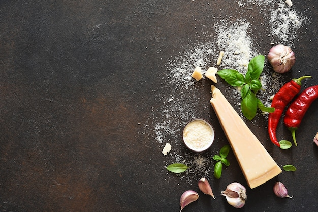 Parmesan cheese with basil, garlic and chili on a concrete background. ingredients for the sauce, top view.