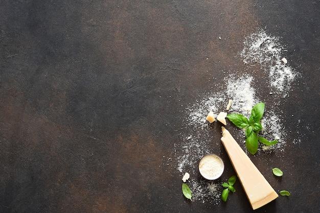 コンクリートの背景にバジルとパルメザンチーズ。ソースの材料、上面図。