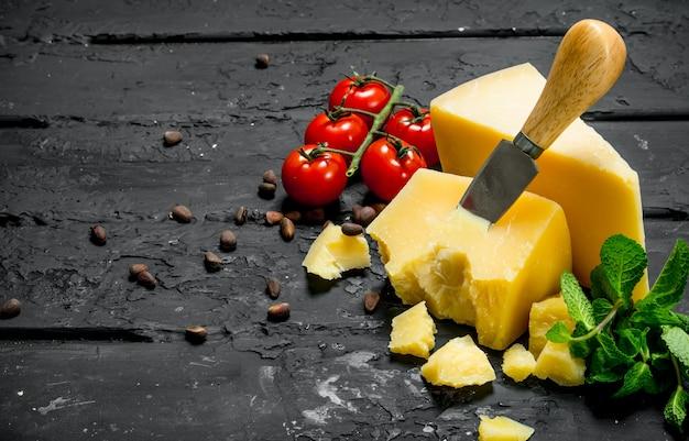 トマト、松の実、ミントの葉を添えたパルメザンチーズ。黒の素朴な背景に。