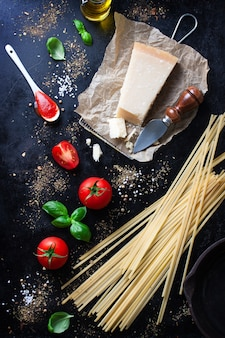 Parmesan pasta recipe with a piece of cheese and raw pasta and other ingredients