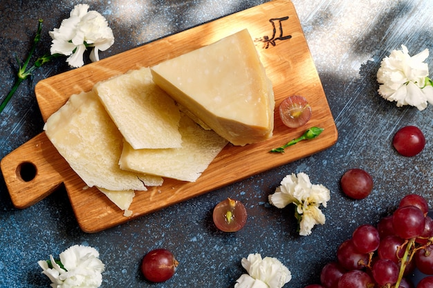 Parmigiano cheese on wooden cut board with grape berries