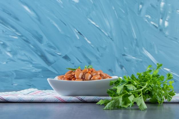 青い背景に、ティータオルの上にパセリと豆のボウル。